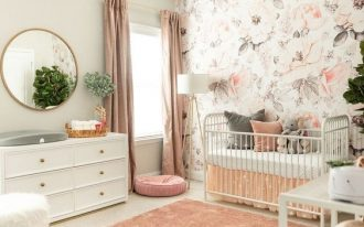 nursery, cream rug flor, pink rug, white wall, flowery accent, chandelier, white cabinet, white fur stool, white shelves