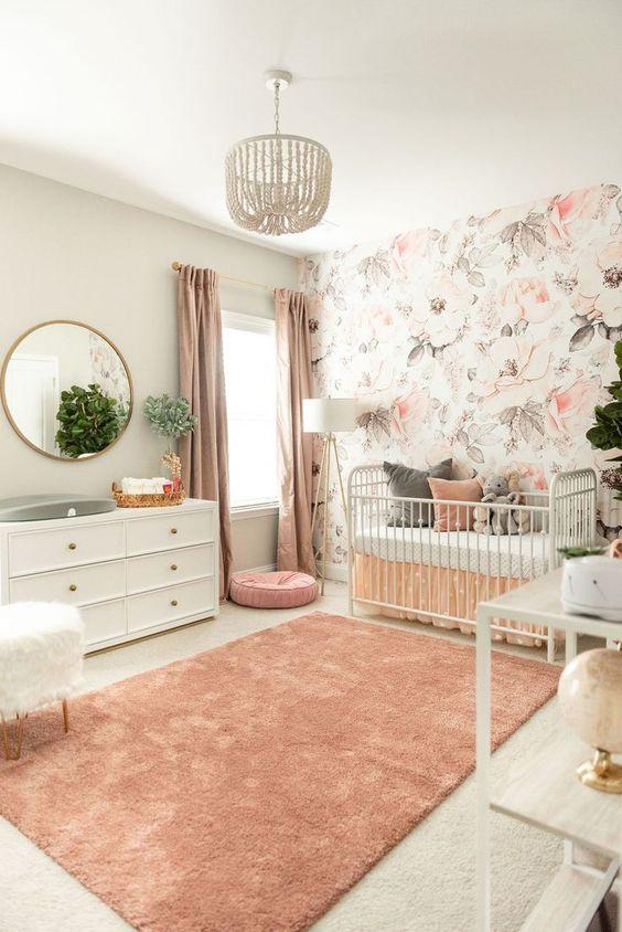 nursery, cream rug flor, pink rug, white wall, flowery accent, chandelier, white cabinet, white fur stool, white shelves