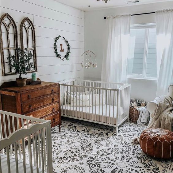 nursery, white patterned rug, white shiplap wall, white cribs, brown cabinet, leather ottoman