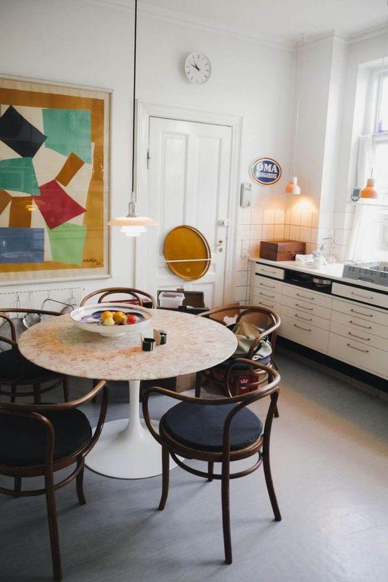open kitchen, grey seamless floor, white wall, white bottom cabinet, white marble round table, black brown chairs, white pendant