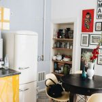 Open Kitchen, Patterned Floor Tiles, Light Grey Wall, White Wall, Black Round Table, White Midcentury Modern Chairs, White Fridge, Yellow Bottom Cabinet