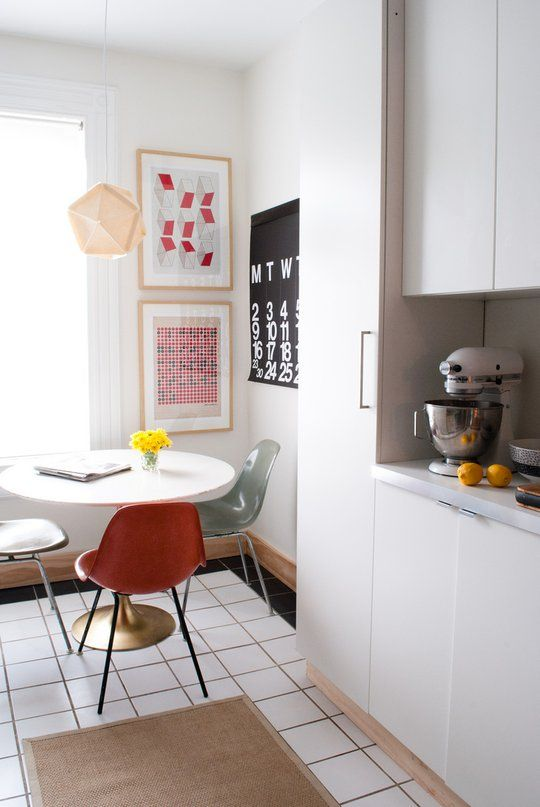 open kitchen, white square floor tiles, white wall, white modern cabinet and cupboard, white round table, colorful modern chairs