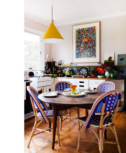 open kitchen, wooden floor, white wall, yellow pendant, blue chairs, wooden round table, white bottom cabinet, dark green backsplash, floating shelves