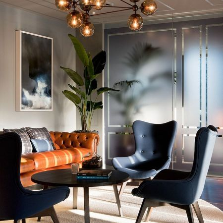 orange sofa with rufted back, navy chairs, black round coffee table, cream wall, brown glass chandelier