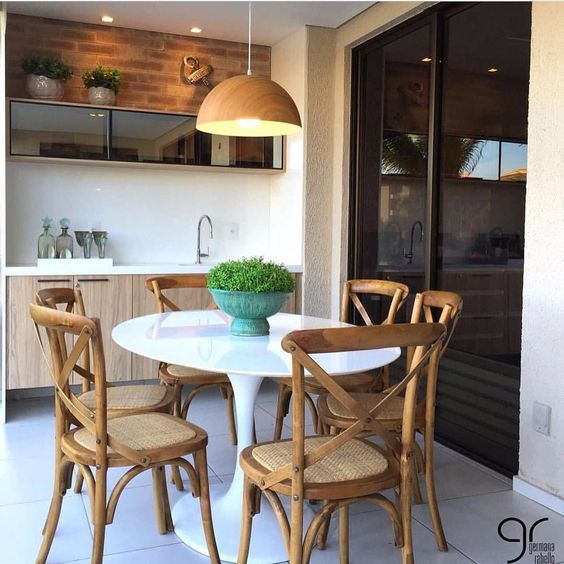 patio, white floor tiles, white wall, wooden vanity with white counter top, white round tulip table, wooden chairs with rattan seating, wooden pendant, black glass wall