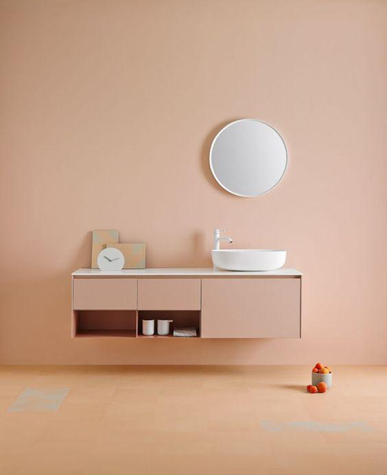 peach wall, peach floor, peach floating cabinet, white counter top, white sink, round mirror