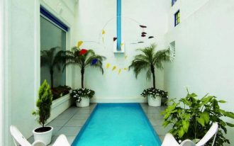 pool, grey floor tiles, white wall, white butterfly chairs, glass window