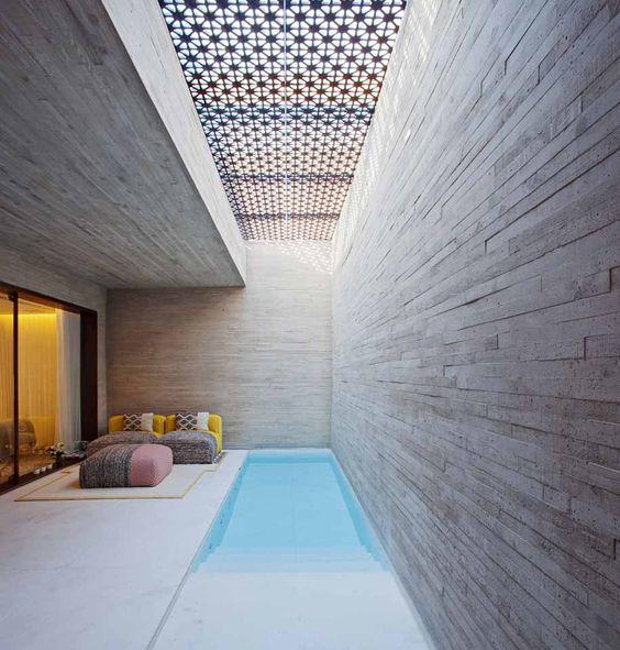 pool, stone wall, light concrete floor, rectangular pool, sofa, ottoman