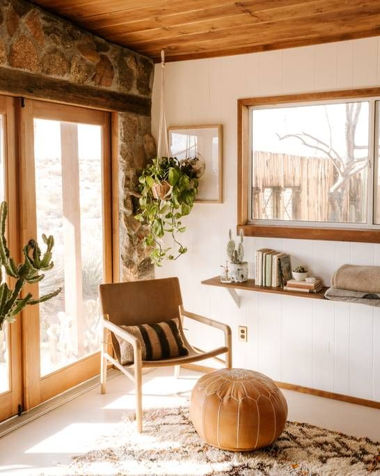 reading corner, white floor, white wall, wooden ceiling, glass window, floating shelf, glass door, brown chair, brown ottoman