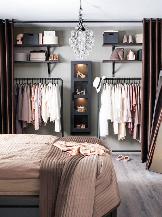 small closet, brown curtain, wooden floor, grey wall, black shelves, rod, chandelier,