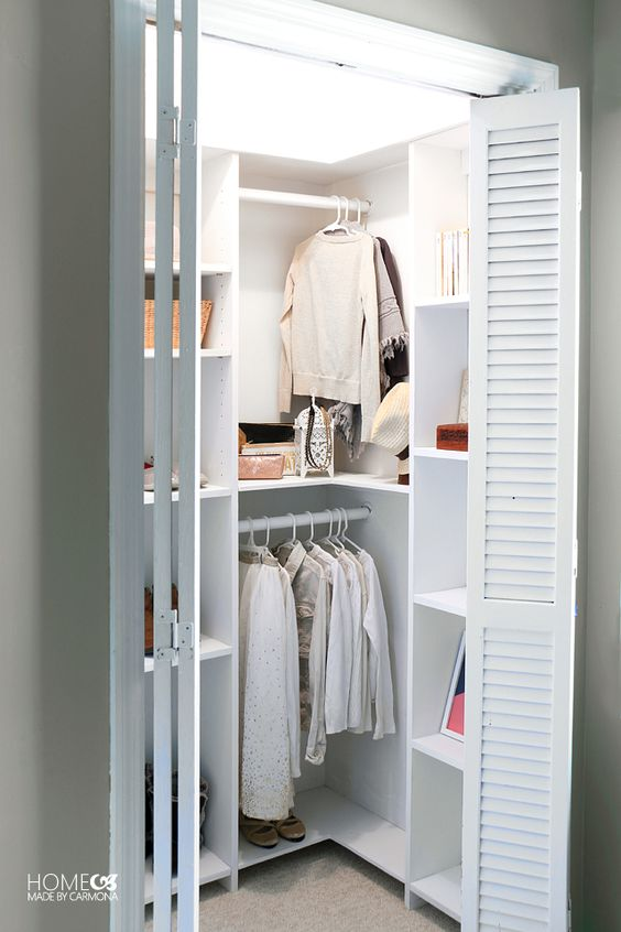 small closet, brown floor, white sliding wooden door, white shelves, row