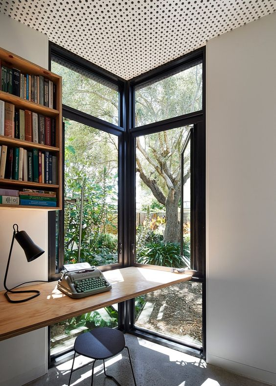study, wooden floating table, black stool, white wall, floating shelves, polka dot ceiling, tall glass window
