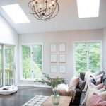 Tall Vaulted Ceiling, Glass Ceiling Window, Dark Wooden Floor, White Black Plaid Floor, White Wall, Chandelier, Black Sofa, Colorful Pillows