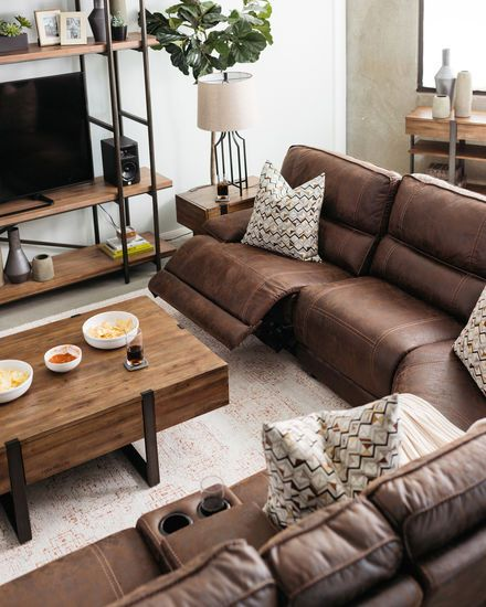 traditional living room, white rug, brown leather sofa, wooden coffee table with metal legs, wooden shelves