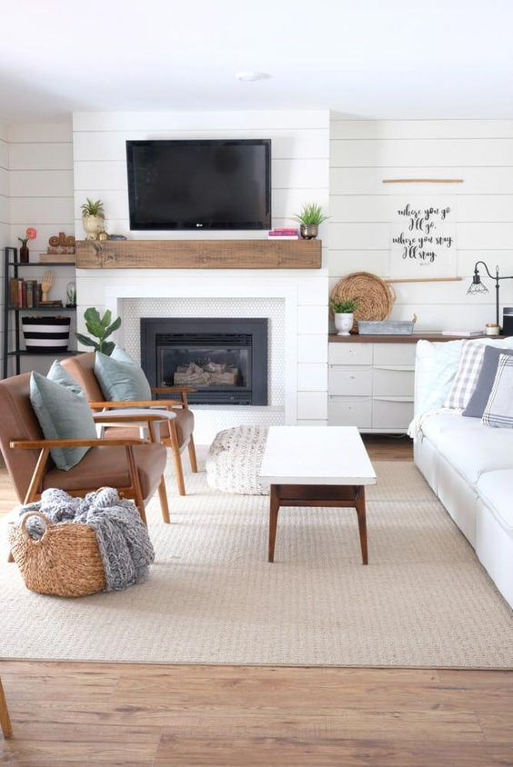 traditional living room, wooden floor, white shiplap, white fireplace, brown leather chair,s, white sofa, white coffee table