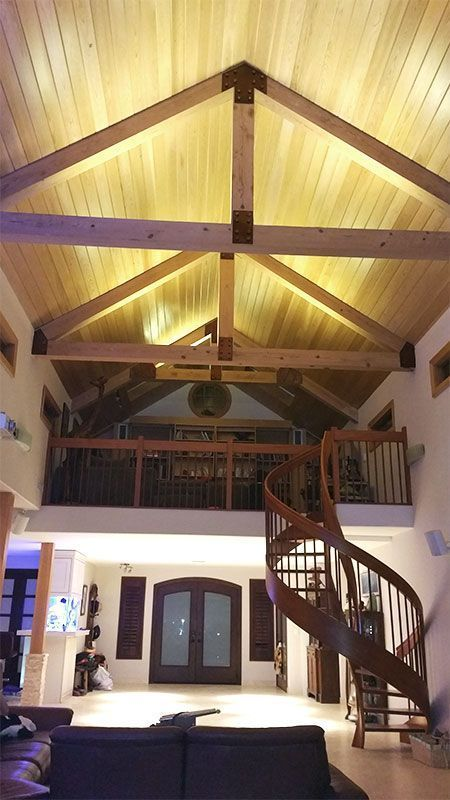 vaulted ceiling, yellow lights on the ceiling, brown floor, black sofa, stairs