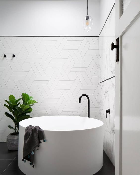 white round soaking tub, white geometrical wall tiles, white marble wall, glass melted pendant, black floor, black faucet