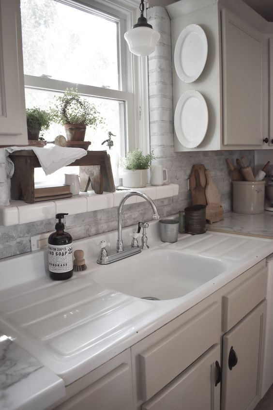 white sink, white cabinet, white exposed brick, white framed window