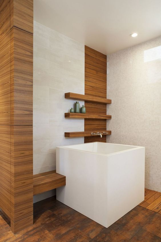 white square soaking tub, wooden floor, white wall, wooden shelves, cream marble wall tiles