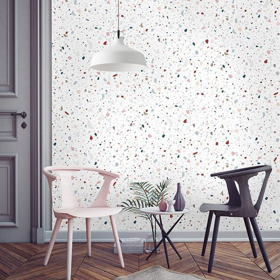 white terrazzo marble on the wall, pink chair, black chair, white coffee table, white pendant, grey door, wooden floor