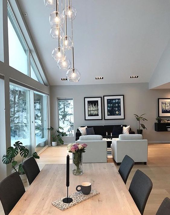 white vaulted ceiling, glass pendants, wooden floor, wooden table, black chairs, black sofa, white chairs