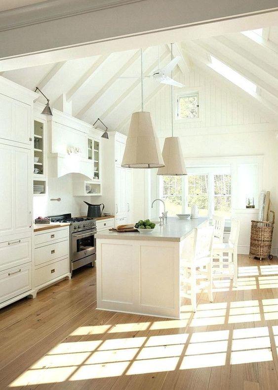 white vaulted ceiling, white wooden beams, white pendants, white cabinet, white island, wooden floor