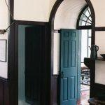 White Wall, Black Curvy Arch, Green Door, Wooden Floor
