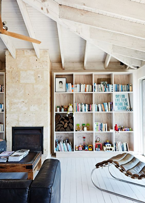 white wooden bookshelves, brown wall, white wooden floor, black sofa, white wooden ceiling, brown leather lounge chair