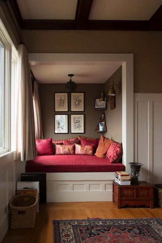 window bed, brown wall, white wainscoting, white bench, red cushion, red pillows, wooden floor, brown wall