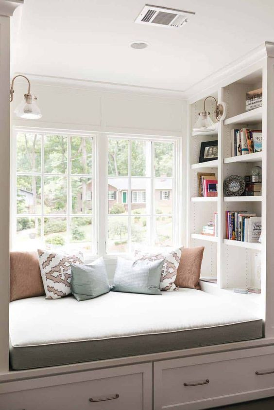window, white cabinet under, white built in shelves, glass window, glass sconces, grey cushion, soft pillows