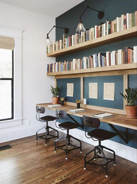 working space, wooden floor, floating wooden shelves, black sconces, floating wooden table, black chairs, white wall