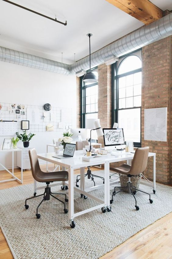 working space, wooden floor, white exposed brick wall, white table, brown office chair, grey rug, black penant, wall decorations