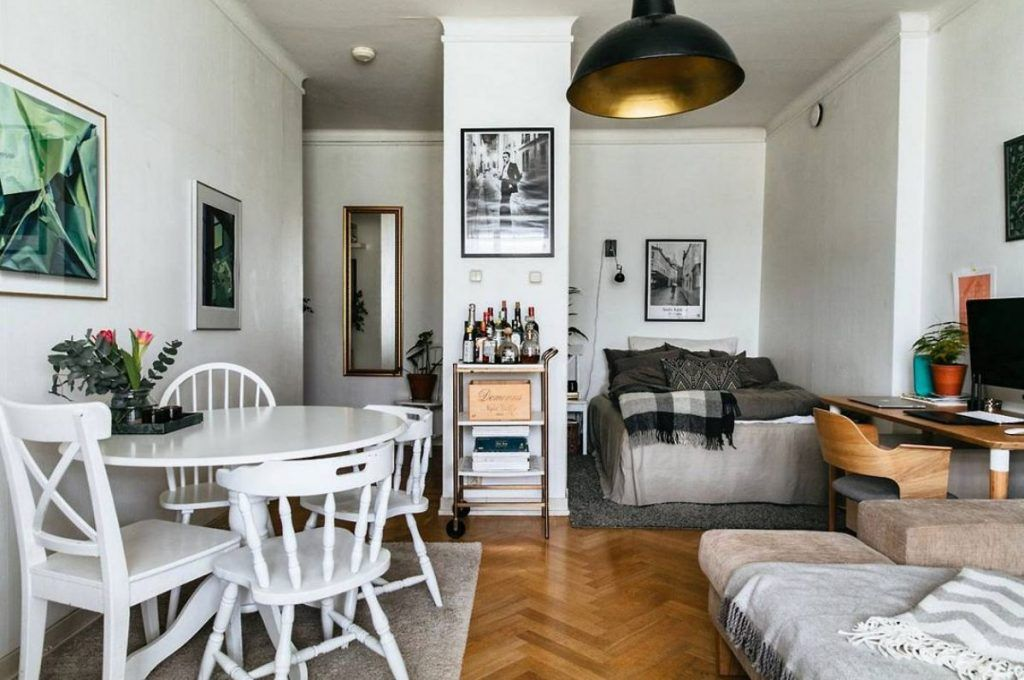 apartment, wooden floor, white wall, white round dining table, white chairs, black pendant, white bed, stidu table