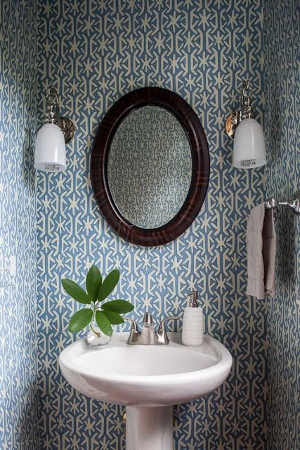 bathroom, blue patterned wallpaper, white sink, round wooden mirror, white sconces