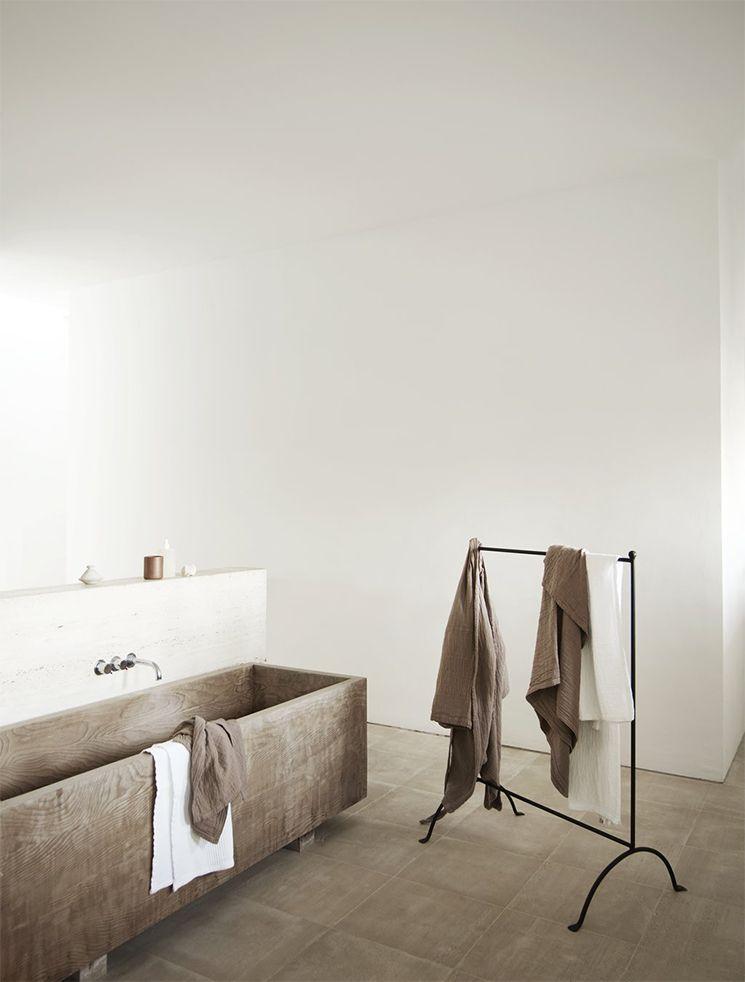 bathroom, brown floor tiles, long narrow brown tub, white walll