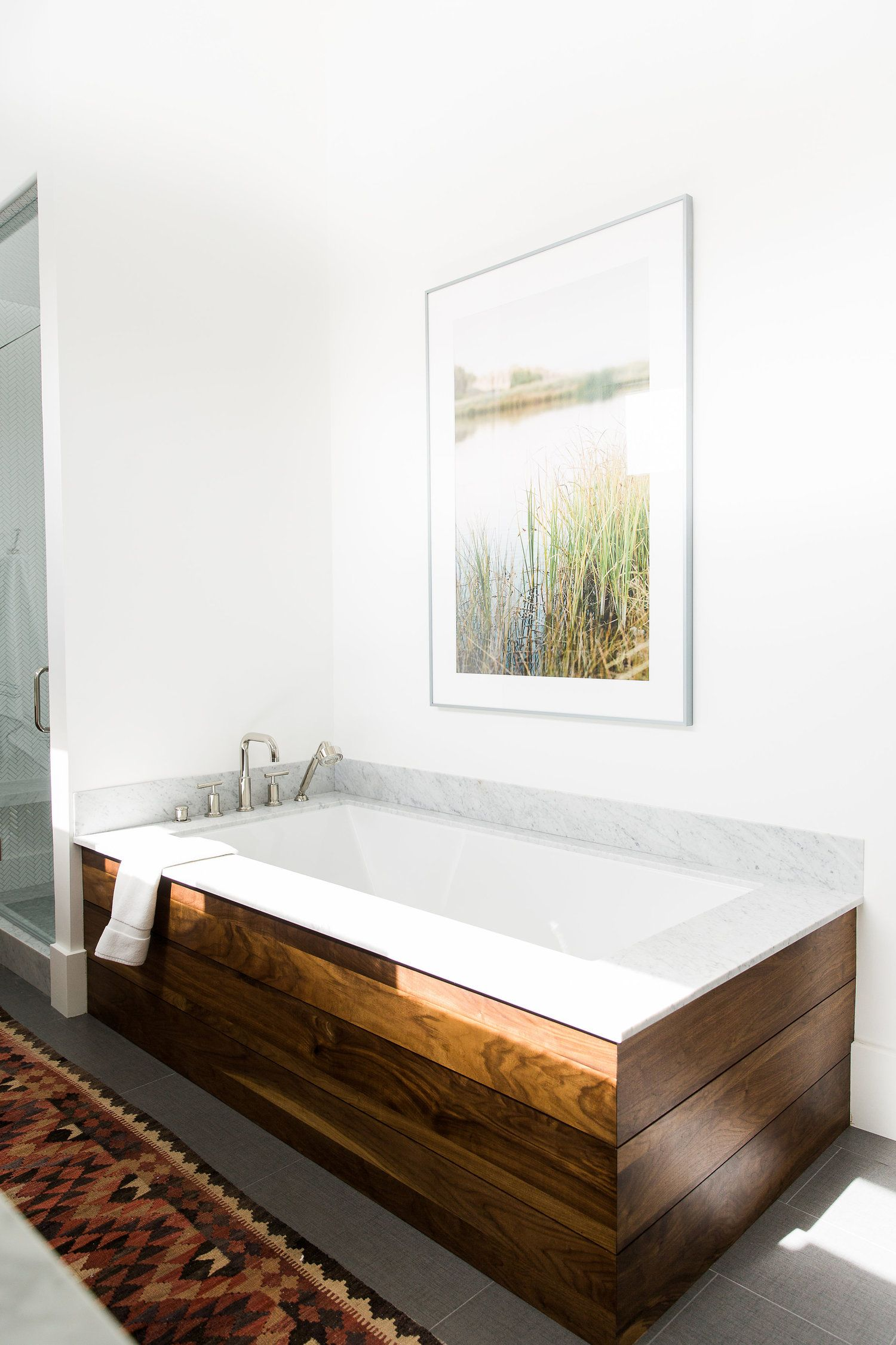 bathroom, grey floor tiles, patterned rug, white wall, wooden covered white tub