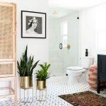 Bathroom, Hexagonal Floor Tiles, White Wall, White Toilet, Patterned Rug, Black Cabinet, Golden Pots, Rattan Cabinet