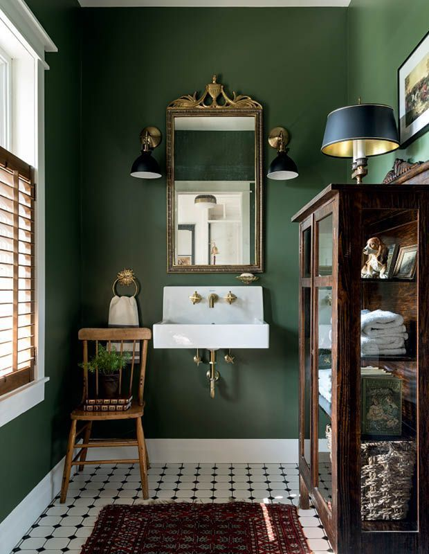 bathroom, white floor tiles, greeen wall, white floating sink, wooden chair, black sconces, golden framed mirror, wooden cabinet with glass