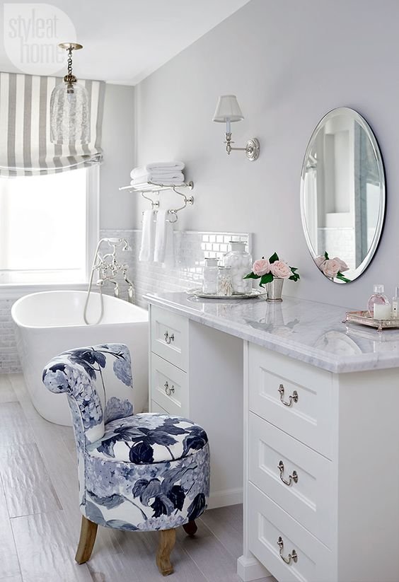 bathroom, white floor tiles, white wall, white cabinet, white tub, flowery chair, white marble top, round mirror, glass chandelier, white sconces
