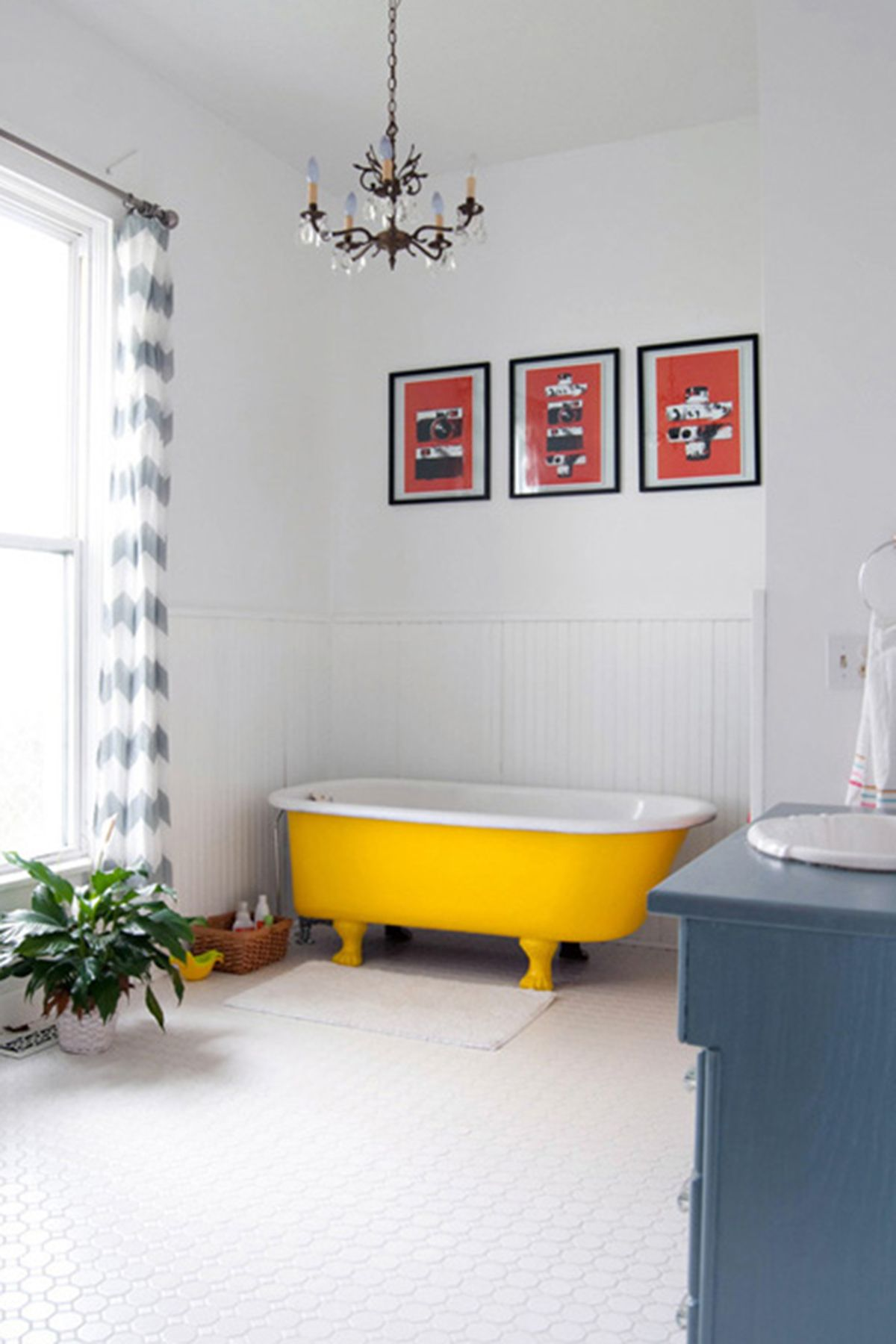 bathroom, white floor tiles, white wall, yellow tub, blue cabinet, white sink, white wainscoting wall