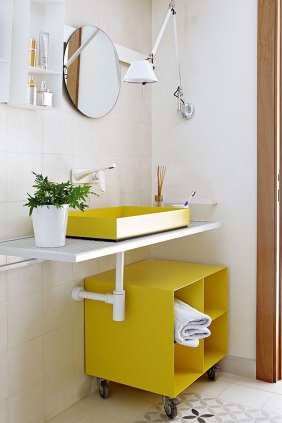 bathroom, white vanity counter, yellow square sink, yellow square shelves, white wall, white floaitng shelves, round mirror, white floor tiles