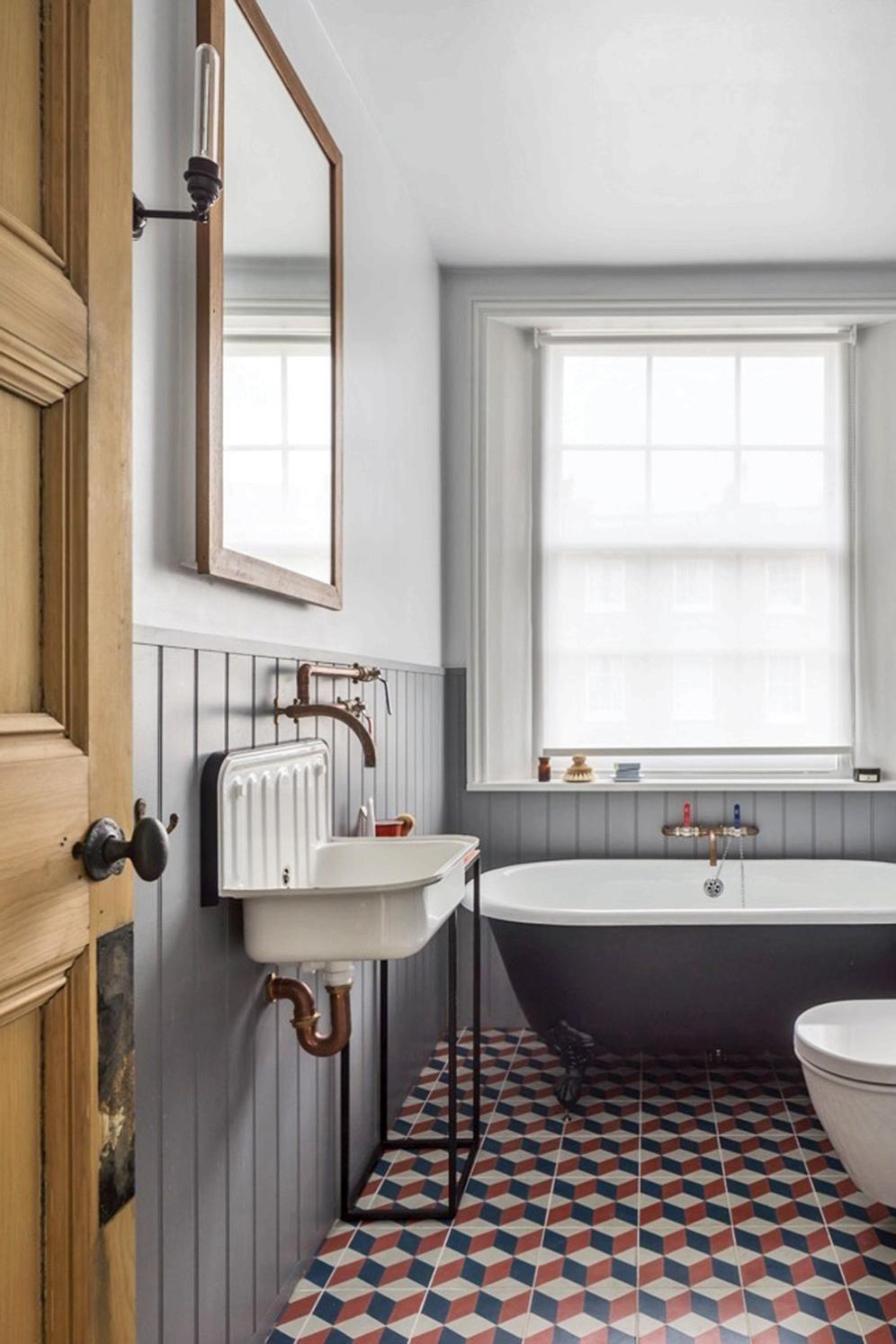 bathroom, white wall, grey wainscoting, black tub, white vintage sink, patterned floor tiles