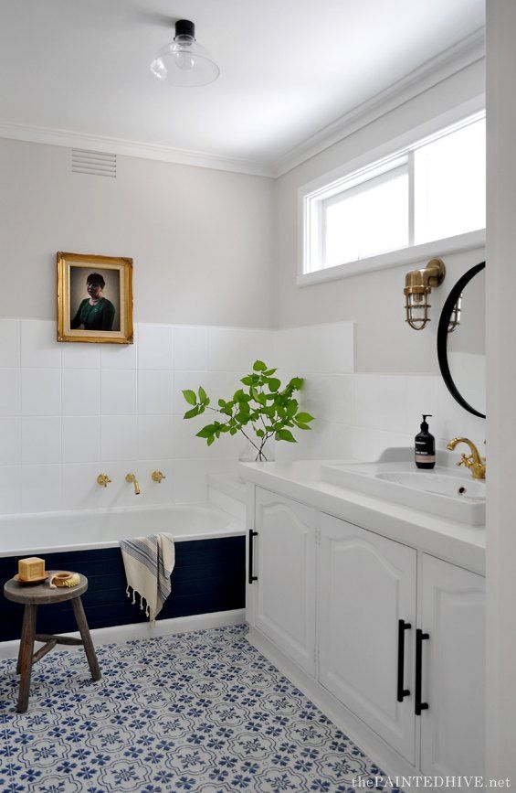 bathroom, white wall, white wall tiles, black tub, white cabinet, white sink, golden faucet, black round mirror