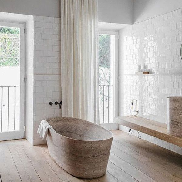 bathroom, wooden floor, floating wooden bench, brown marble tub, white subway wall tiles, glass window