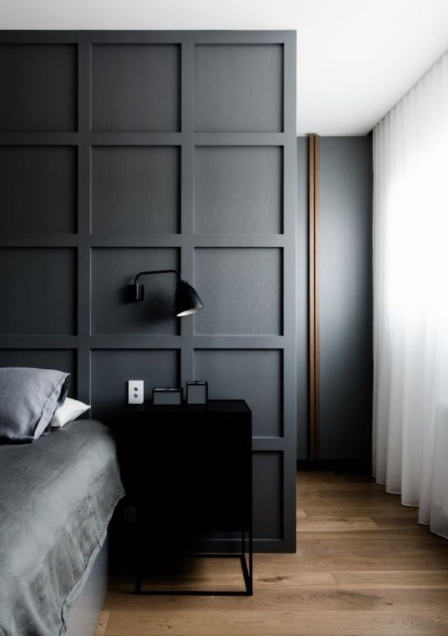 bedroom, black accent wall, black side cabinet, wooden floor, grey bedding, black sconce