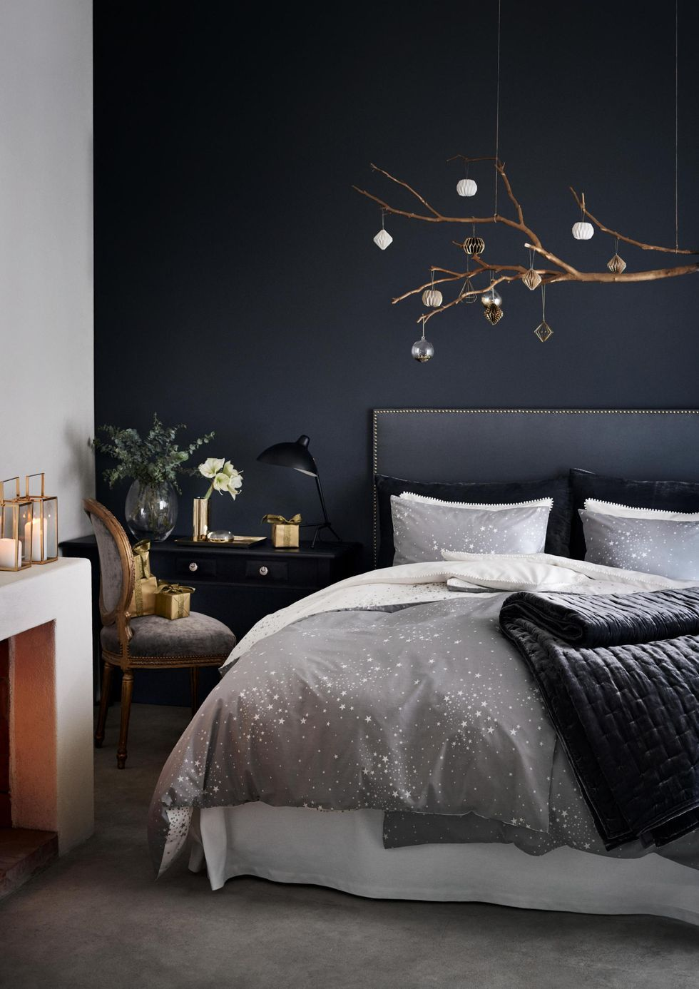 bedroom, black accent wall, white wall, white bedding, black wooden table, black table lamp, grey chair, accessories