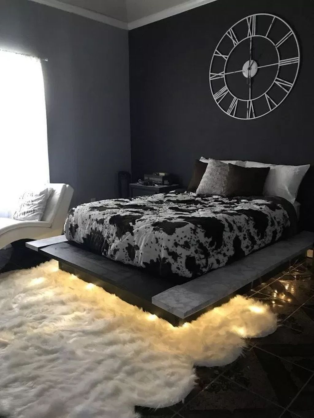 bedroom, black wall, black bed platform, white lounge chair, white rug, black floor, black bedside cabinet