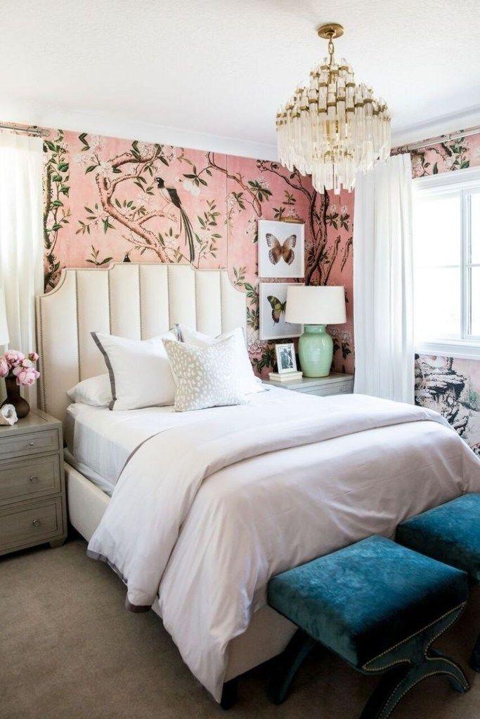 bedroom, grey floor, pink flower wallpaper, white headboard, white bedding, grey wooden side cabinet, white chandelier, blue velvet ottomans