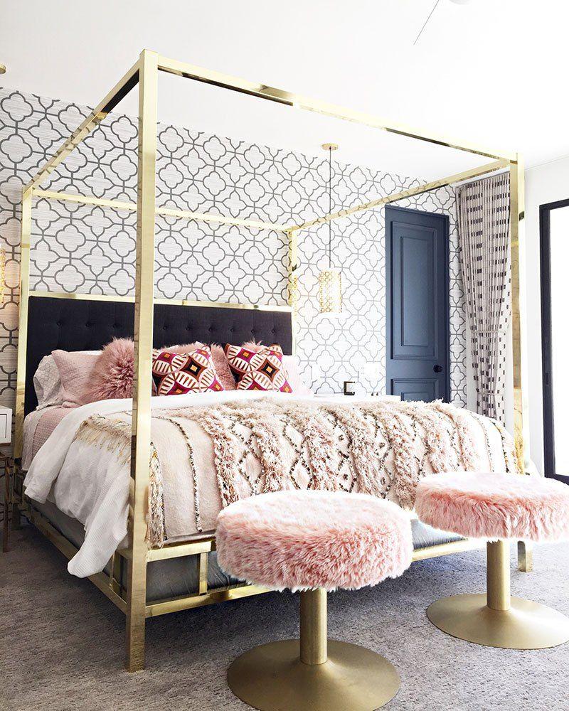 bedroom, grey floor rug, geometrical wallpaper, golden bed platform, pink fur stool, side table, black door