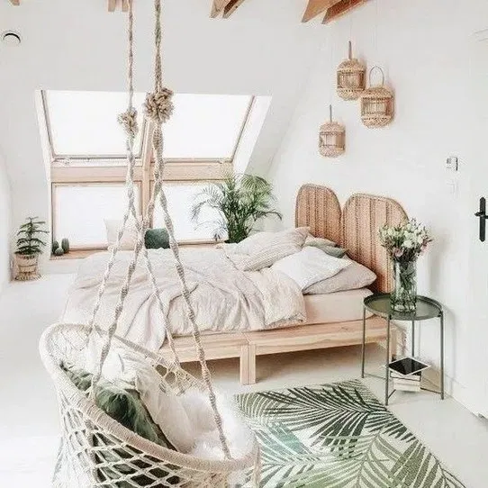 bedroom, white floor, white wall, wooden bed platform, rattan headboard, white rattan swing, glass window on vaulted ceiling